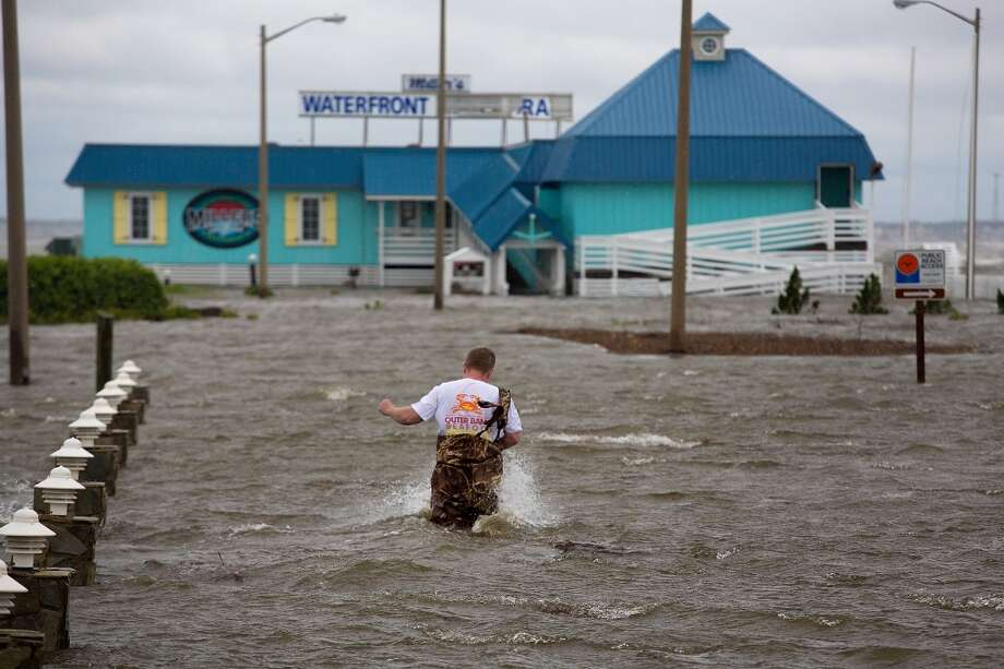 North Carolina: Bryan Wilson, owner of Millerís Waterfront restaurant, braves floodwaters to check the damage to his property as wind from the Hurricane Arthur pushes water to his parking lot in Nags Head, N.C. Friday, July 4, 2014. Arthur struck North Carolina as a Category 2 storm with winds of 100 mph late Thursday, taking about five hours to move across the far eastern part of the state. Photo: Hyunsoo Leo Kim, Associated Press