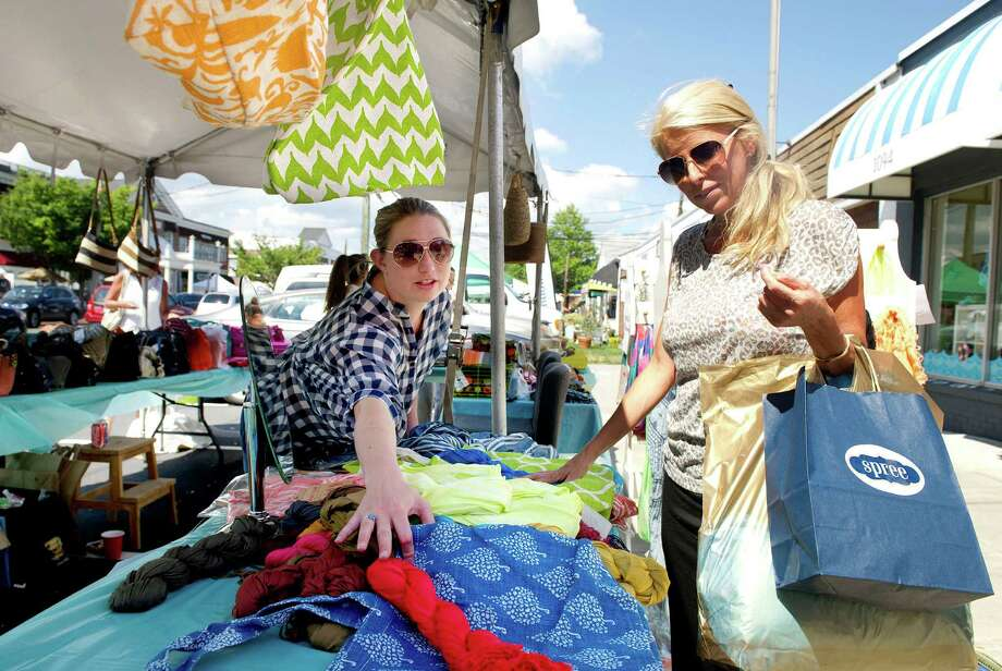 Holly Strongwater, right, talks with Amanda England, left, of Beadz Boutique as Strongwater shops at the Darien Chamber of Commerce's sidewalk sale on Post Road on Friday, July 11, 2014. The event continues Saturday, July 12, 9 a.m. to 5 p.m. Photo: Lindsay Perry / Stamford Advocate