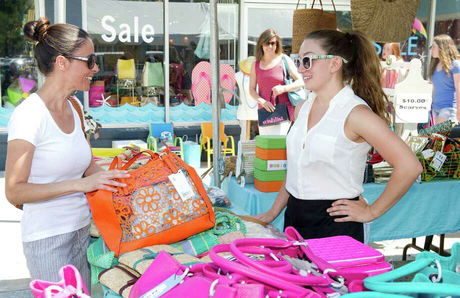 Allie Amarillo, left, looks at a purse as she talks with Jeanette Prieston of Beadz Boutique during the Darien Chamber of Commerce's sidewalk sale on Post Road on Friday, July 11, 2014. The event continues Saturday, July 12, 9 a.m. to 5 p.m. Photo: Lindsay Perry / Stamford Advocate