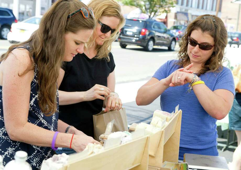 From left,Colleen Vallely, Stacy Infantas and Jessica Sobin look at soaps and lotions from Komfort Zone LLC. during the Darien Chamber of Commerce's sidewalk sale on Post Road on Friday, July 11, 2014. The event continues Saturday, July 12, 9 a.m. to 5 p.m. Photo: Lindsay Perry / Stamford Advocate