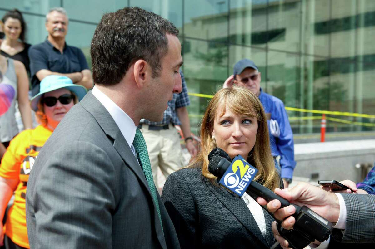 Former animal shelter Director Laurie Hollywood speaks to the media with her attorney, Mark Sherman, outside State Superior Court in Stamford, Conn., after being arraigned on three counts of reckless endangerment on Thursday, July 10, 2014.