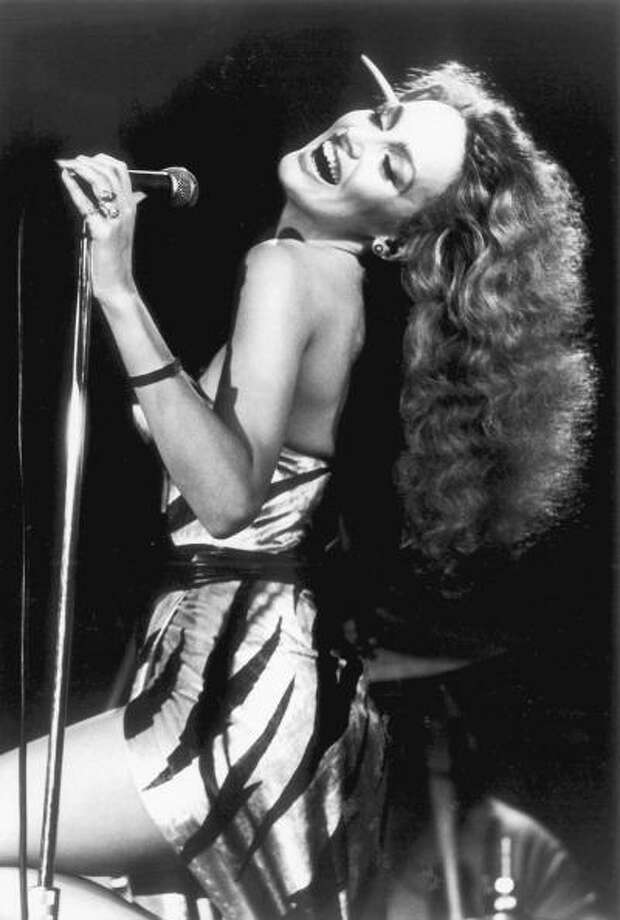 Fashion model Jerry Hall, seen here performing on stage with Bryan Ferry in 1977, age 21.  Hall was one of the most successful models of the mid-to-late '70s. Photo: Michael Putland, Getty Images / 1977 Michael Putland