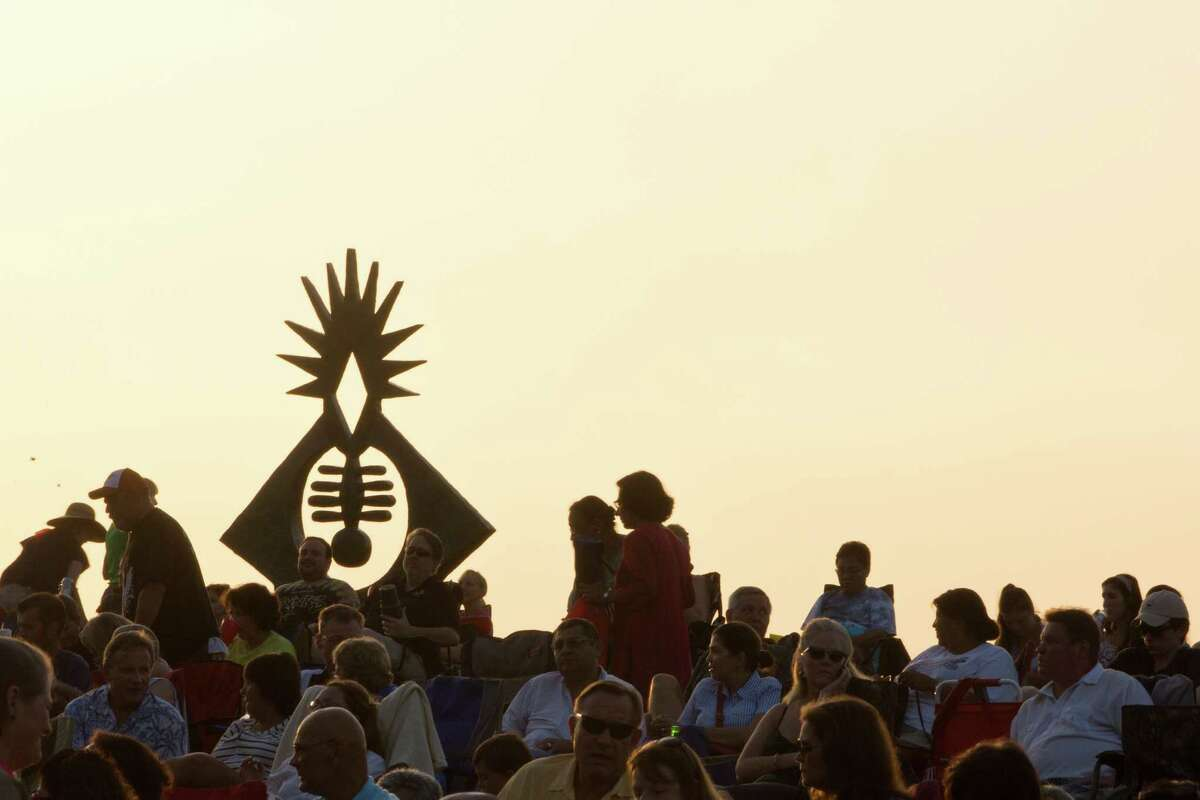 The Atropos Key sculpture is silhouetted by the afternoon light and surrounded by Miller Outdoor Theatre audience at the Hill. The Atropos Key was made out of bronze and concrete, and created in 1972 by Hannah Holliday Stewart. Wednesday, July 2, 2014, in Houston. ( Marie D. De Jesus / Houston Chronicle )