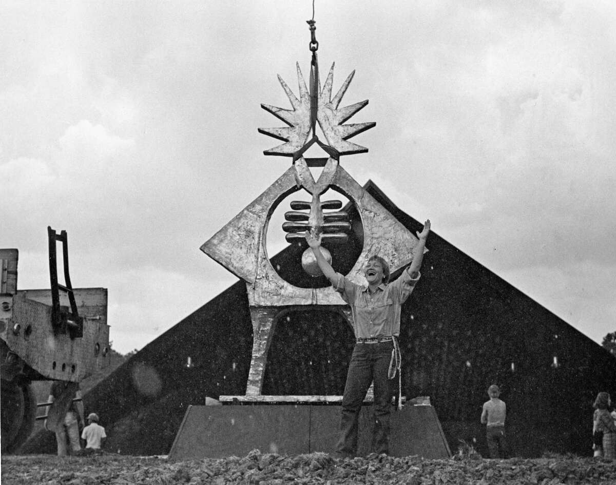 """Sculptor Hannah Holiday Stewart reacts joyfully as her monumental bronze """"Atropos Key"""" is installed on the hill at Miller Outdoor Theater in Hermann Park in 1972."""