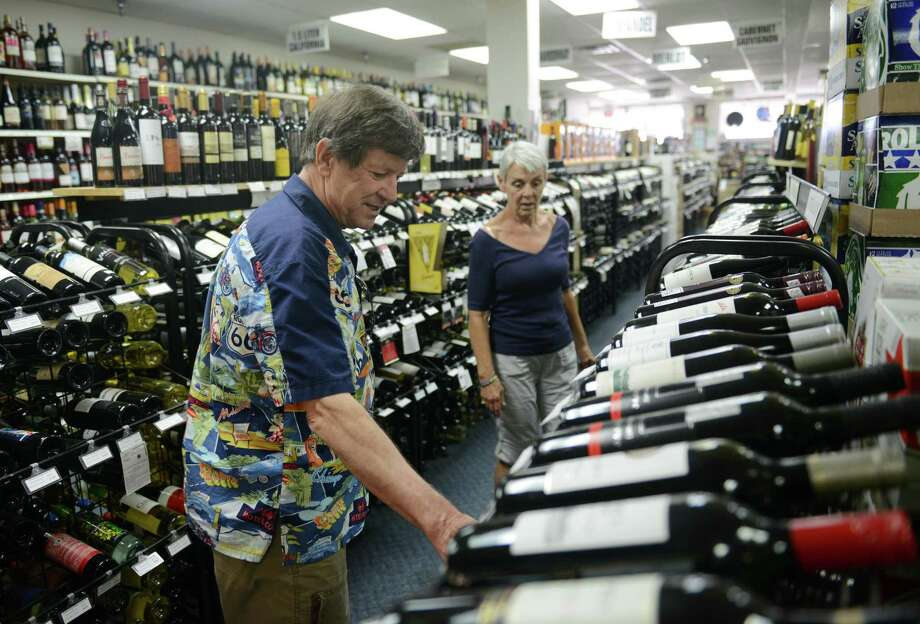 Tom and Donna Black, of Reynoldsburg, Ohio, browse the selection of wine at Central Package in Bethel, Conn. Friday, July 11, 2014.  The family-owned liquor store is celebrating its 50th anniversary this year. Photo: Tyler Sizemore / The News-Times