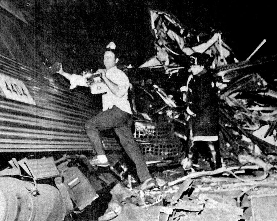 Rescue workers look for survivors following the collision of two Penn Central commuter trains near Hoyt Street in Darien on Aug. 20, 1969. Four people were killed and more than 40 were injured in the accident which prompted calls for increased safety. Photo: File Photo/Tom Ryan / Stamford Advocate File Photo
