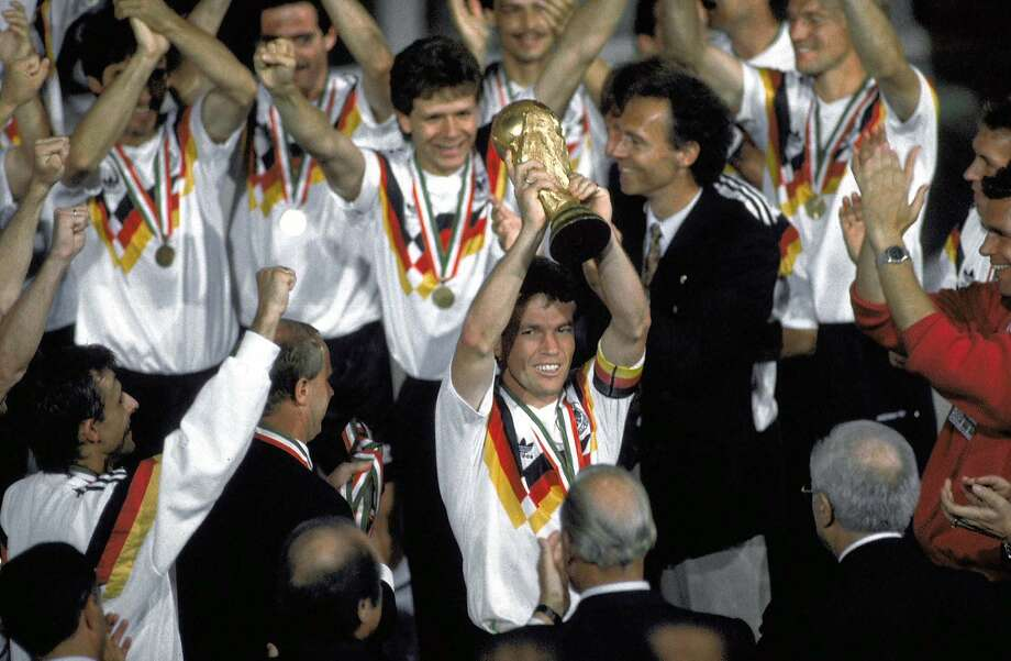 Germany captain Lothar Matthaeus, with coach Franz Beckenbauer behind him, hoisted the World Cup trophy in 1990. Photo: Carlo Fumagalli, Associated Press
