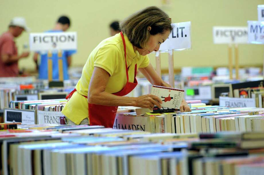 Toni Earnshaw works on finalizing the display for the Friends of the C.H. Booth Library 39th annual book sale Friday morning, July 11, 2014.