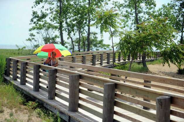 Susan Williams, of Bridgeport, carries her beach umbrella along the boardwalk after spending the afternoon at Pleasure Beach, a 71 acre peninsula betweeen Bridgeport and Stratford which reopened to the public Saturday, June 28, 2014, after being closed for nearly two decades. Photo: Autumn Driscoll / Connecticut Post