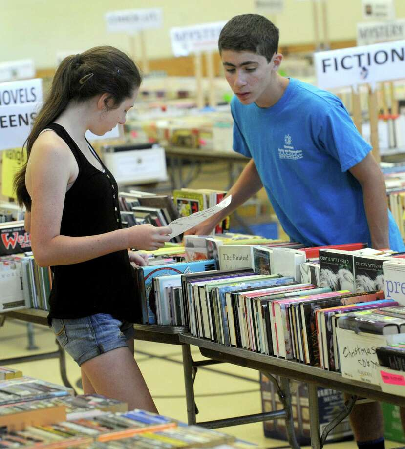 Brielle and Brandyn Chieffo, 15, of Newtown, Conn. are part of a team of volunteers finalizing the displays for the 39th annual Friends of the C.H. Booth Library booksale that opens Saturday morning and runs through Wednesday at Noon, at the Reed Intermediate School in Newtown. Friday, July 11, 2014. Photo: Carol Kaliff / The News-Times