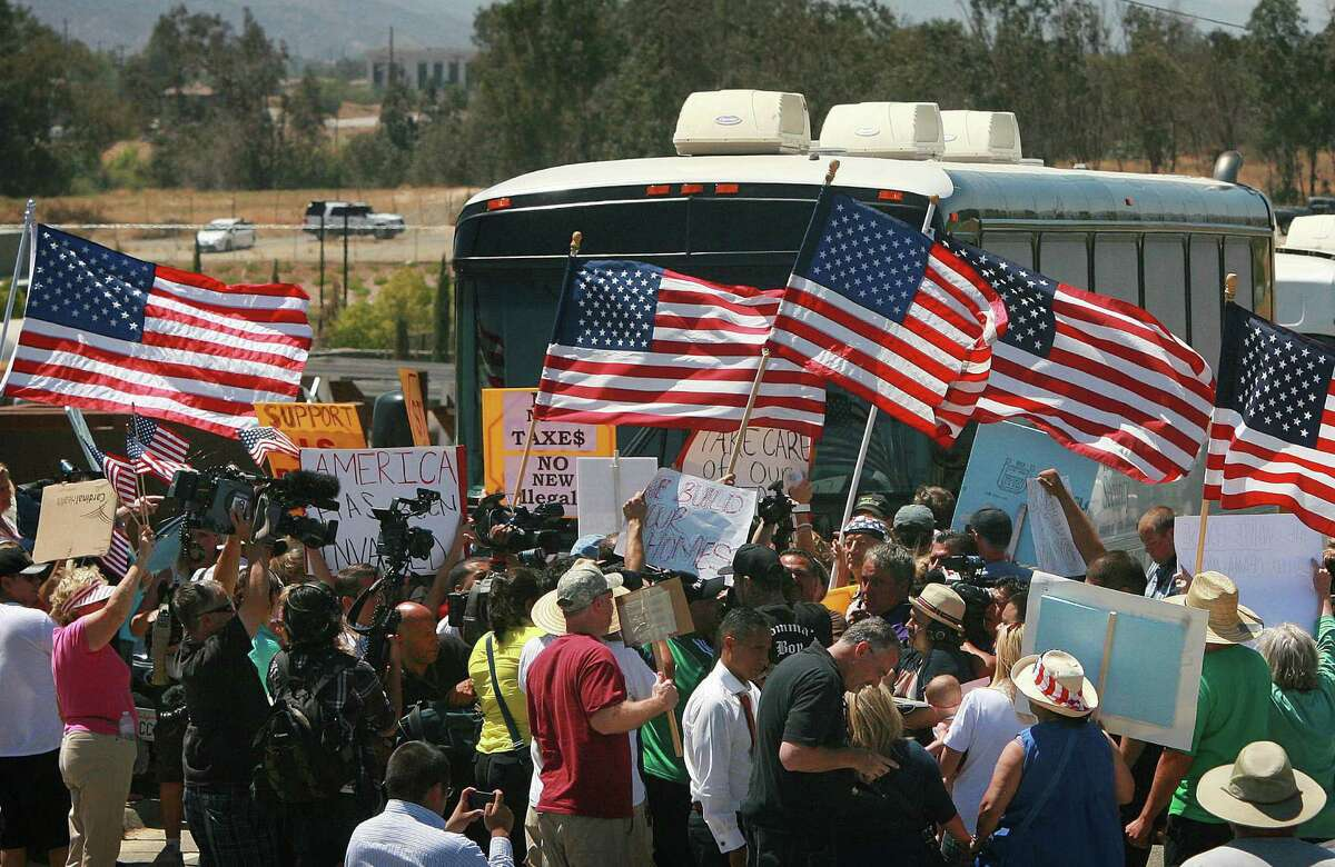Protesters turn back three buses carrying 140 immigrants as they attempt to enter a U.S. Border Patrol station for processing earlier this month in Murrieta, Calif.