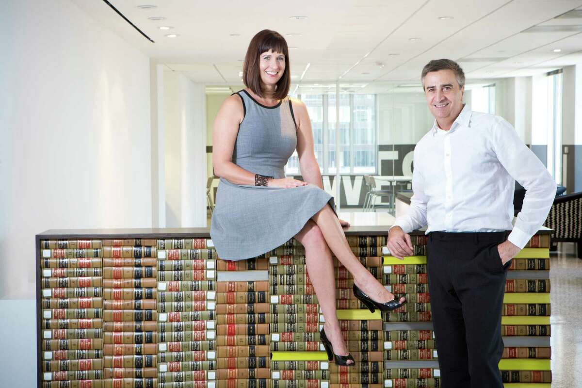 Kelie Mayfield and Erick Ragni have their portrait taken by a custom reception desk made out of repurposed 495 law volumes dating form 1904 thru the 1980's. Mayfield and Ragni are interior designers helping their clients visually express their identity and corporate brand. Wednesday, July 9, 2014, in Houston. ( Marie D. De Jesus / Houston Chronicle )