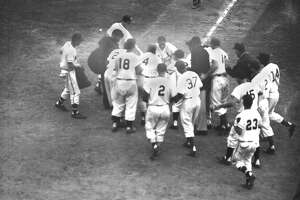Stan Musial crosses home plate after slamming the first pitch of the 12th inning over right field screen for the game-winning homer in Milwaukee on July 12, 1955.  Musial's homer gave the National Legue All-Stars a 6-5 victory.  Musial is greeted by jubilant teammates.  (AP Photo) Ran on: 07-01-2007 Stan Musial is given a hero's welcome at home plate after he ended the 1955 All-Star Game with a 12th-inning HR.