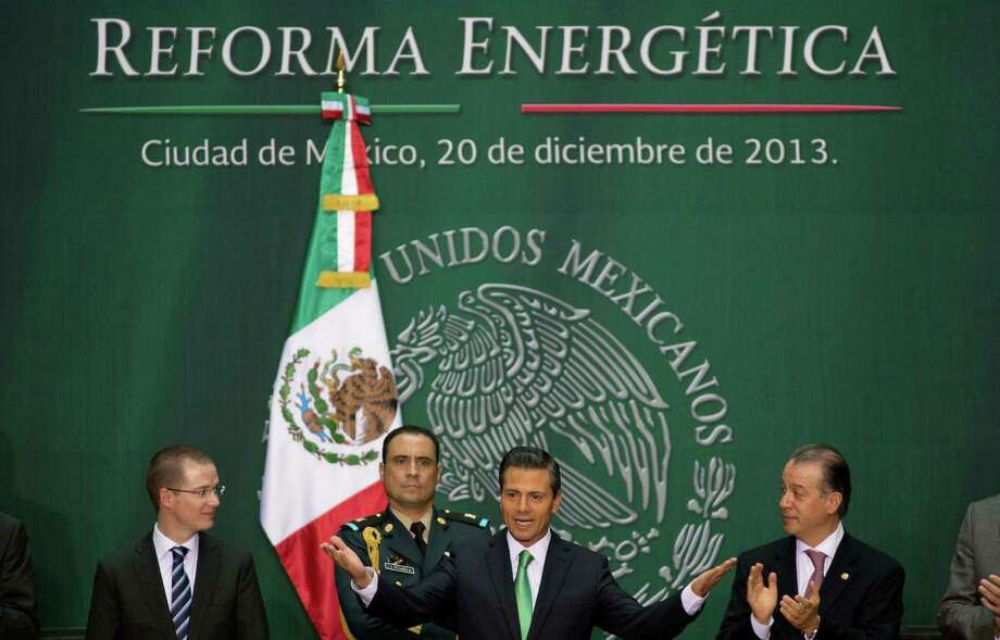 Mexico's President Enrique Pena Nieto greets attendees at the signing ceremony for the approved energy reforms at the National Palace in Mexico City, Friday, Dec. 20, 2013. The sweeping reforms approved by state legislators allow private companies to explore for and produce oil and gas, capping a remarkable series of legislative victories by the Mexican leader. (AP Photo/Eduardo Verdugo) Photo: Eduardo Verdugo, STF / AP
