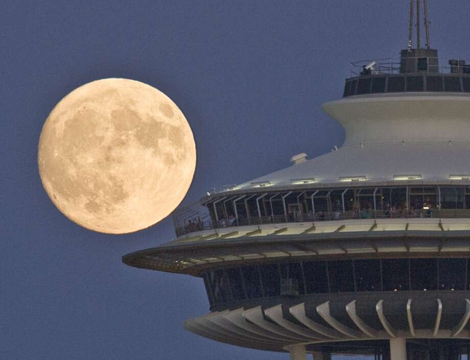 Excited for a supermoon trio? Here's a look at full moons (super and otherwise) for a taste of what's in store this  summer, beginning July 12.   One thing to know: NASA scientists say it's hard to see the difference between a supermoon and a normal full moon. Why is that? (Photo: Supermoon over Seattle, 2008).  Photo: Grant Haller, P-I File