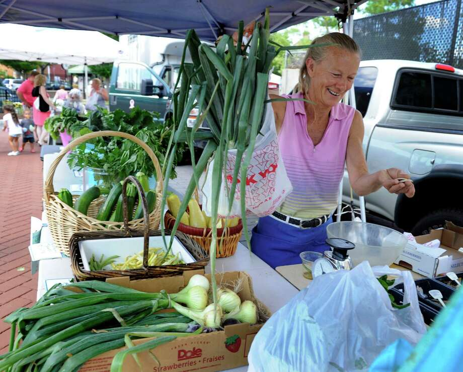 Sandy Wityak, owner of Daisy Mac Gardens in Danbury, Conn, a vender at the Danbury farmers market, holds wooden tokens received from a customer Friday, July 11, 2014. Organizers of the farmers market are reaching out to more people of modest means by offering vouchers to encourage healthy eating. Photo: Carol Kaliff / The News-Times