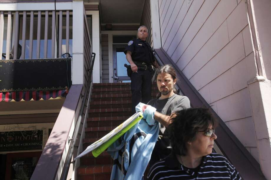 San Francisco police officer M. Faliano clears out protesters from a private balcony and staircase during a protest organized by Eviction Free SF against David McCloskey at his company, Urban Green Investments' San Francisco headquarters July 9, 2014 in San Francisco, Calif. Photo: Leah Millis, The Chronicle