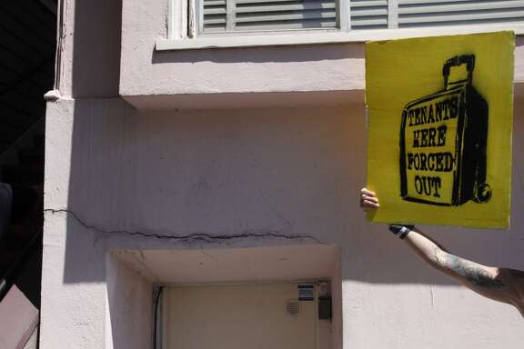 "A protester who preferred not to be named holds up a sign during a protest organized by Eviction Free SF against David McCloskey at his company, Urban Green Investments' San Francisco headquarters July 9, 2014 in San Francisco, Calif. According to Eviction Free SF, the company has used the Ellis Act to evict tenants, including a 98-year-old woman named Mary Phillips. Approximately 30 people showed up with the intent to enter Urban Green Investments and confront them about the recent evictions. The building was closed, however, and protesters made speeches from a nearby balcony until police were called to escort them off of the private property. After they were moved, protesters chanted on the sidewalk for about fifteen minutes, vowing to return. ""Ask politely,"" said 'fellow evictee' Benito Santiago, ""if that doesn't work, sound off."""