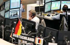 Brokers have a German national flag displayed on their desk at the German stock exchange in Frankfurt, western Germany, few hour before the FIFA World Cup 2014 football match USA vs Germany to be played in Brazil. on June 26, 2014. AFP PHOTO / DANIEL ROLANDDANIEL ROLAND/AFP/Getty Images