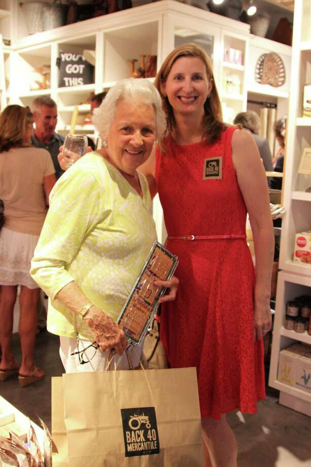 Lesley King, right, co-owner of Back 40 Mercantile, welcomes her neighbor, Old Greenwich native Sue Millard to Back 40's opening party in Old Greenwich on Wednesday evening. Photo: Contributed Photo / Greenwich Time Contributed