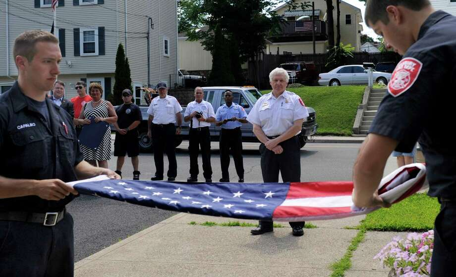 A flag flown over the Danbury Fire Department on New Street is lowered, ceremonially folded and handed to Chief Geoff Herald  Friday, July 11, 2014. The flag retirement ceremony maked the end of an almost 40-year career in firefighting for Herald. He was named chief in 2007.  Folding the flag are firefighters Joe Capalbo, left, and Dan Mansdorf. Photo: Carol Kaliff / The News-Times