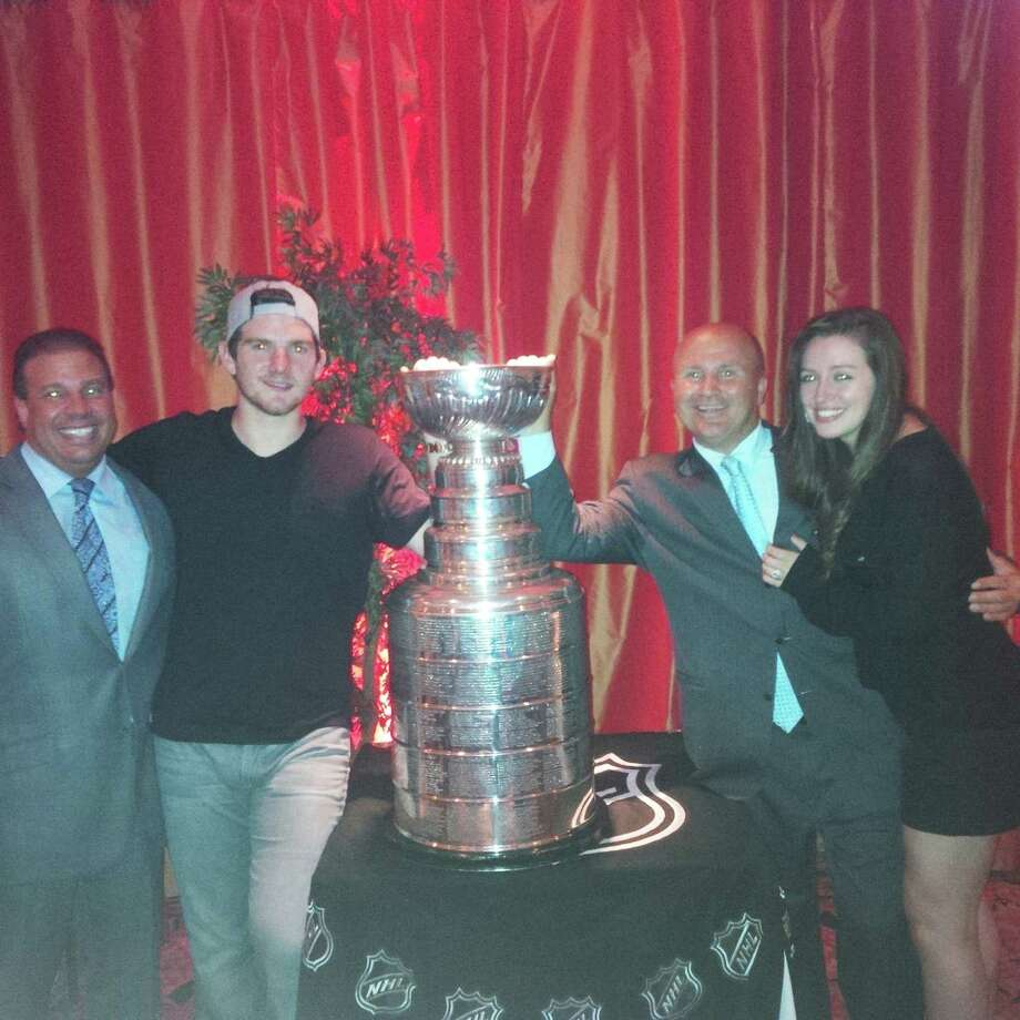 Goalie Jonathan Quick shares the Stanley Cup trophy with, from left, Gabriele's owner Danny Gabriele,Tony Capasso and wife Jaclyn Quick at Gabriele's Italian Steakhouse on Monday night. Photo: Contributed Photo / Greenwich Time Contributed