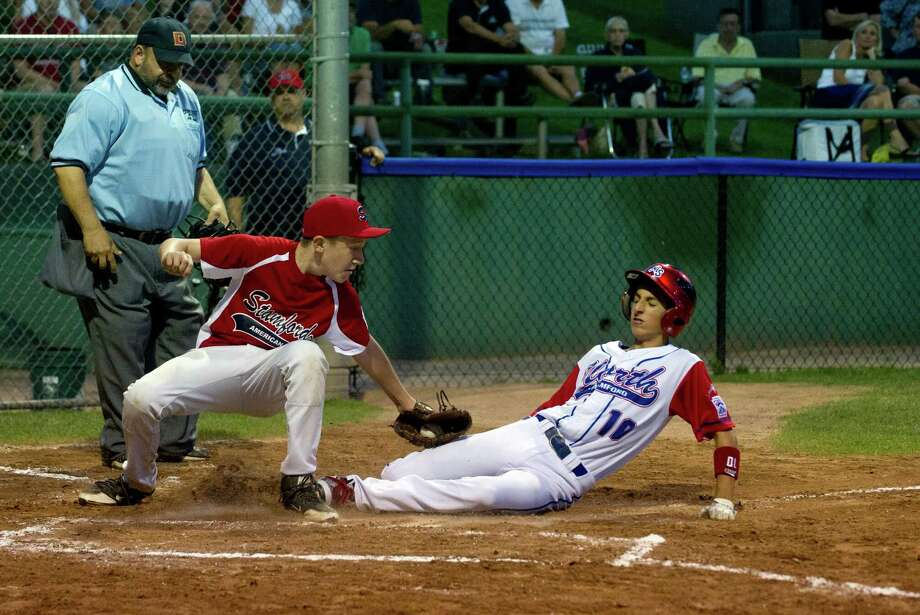 North Stamford's Adam Stone scores a run as Stamford American's Evan Campbell attempts to tag during Friday's District 1 Little League losers bracket final game at Springdale Little League field in Stamford, Conn., on July 11, 2014. Photo: Lindsay Perry / Stamford Advocate