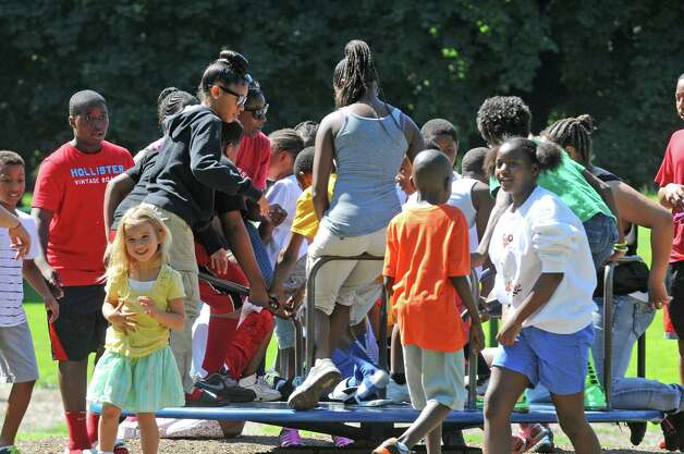 A large group of children, many of the children are with God With You summer camp and some with their parents, gather on a play ground ride at Washington Park Friday, July 11, 2014, in Albany, N.Y. (Michael P. Farrell/Times Union) Photo: Michael P. Farrell