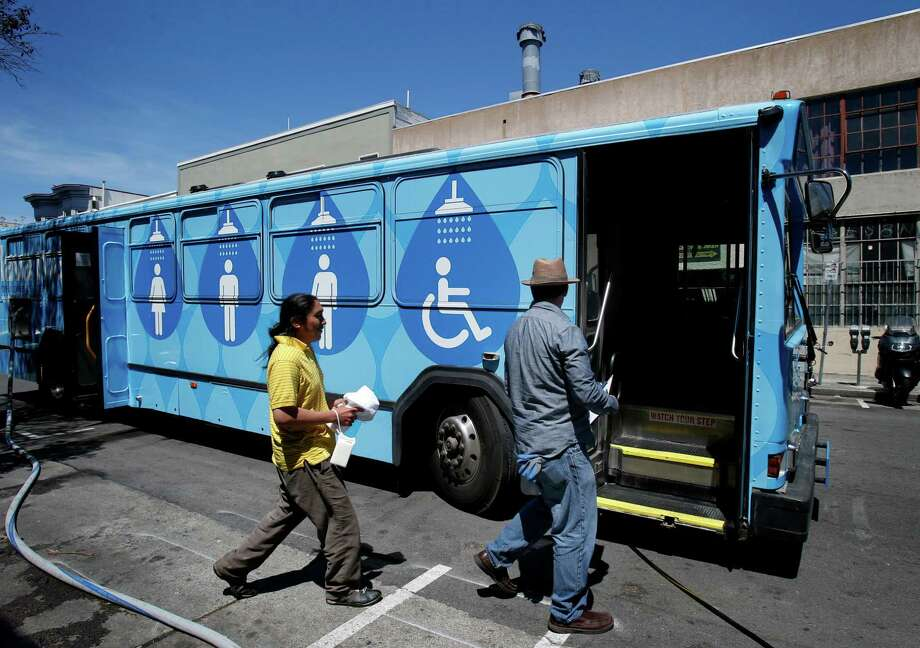 Lava Mae employee Michael McMorrow (right) shows Jose Poot to a shower stall in one of the buses, part of a program that began in July. Photo: Brant Ward / San Francisco Chronicle / ONLINE_YES
