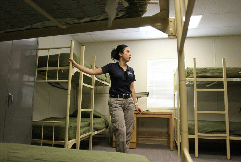 "Barbara Gonzalez, public information officer for Immigration and Customs Enforcement, shows a dormitory where immigrant families are housed at the Artesia Residential Detention Facility inside the Federal Law Enforcement Center in Artesia, N.M. on Friday, July 11, 2014. U.S. Homeland Security Secretary Jeh Johnson visited the facility Friday and warned immigrants that ""we will send you back"" if they try crossing into the country. (AP Photo/Pool, El Paso Times, Rudy Gutierrez) ORG XMIT: TXELP102 Photo: Rudy Gutierrez / POOL The El Paso Times"
