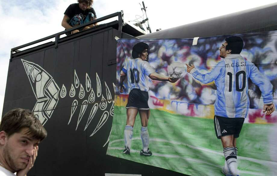 A banner shows Argentina's greatest players: Diego Maradona (left), who led Argentina to the 1986 title, and Lionel Messi. Photo: Rodrigo Abd / Associated Press / AP