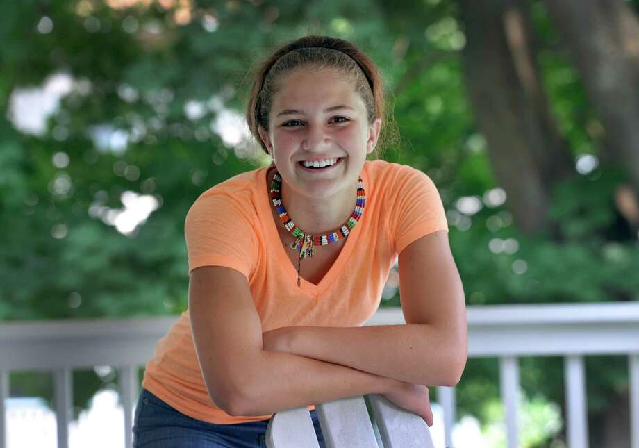 Lily Daniels, 14, of Bethel, Conn., visited Kenya earlier this summer.  She is wearing a necklace given to her by the grandmother of the Kenyan girl she sponsored.  She is photographed on the front porch of her family's home in Bethel. Photo: Carol Kaliff / The News-Times