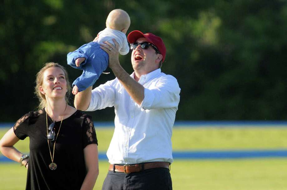 Case Fell of Saratoga Springs, right, tosses his 5-month-old son, Harrison Fell, during a break in the polo match on Friday, July 11, 2014, at the Saratoga Polo Association in Saratoga Springs, N.Y. At left is Harrison's mother, Lindsay Fell. (Cindy Schultz / Times Union) Photo: Cindy Schultz / 00027423A