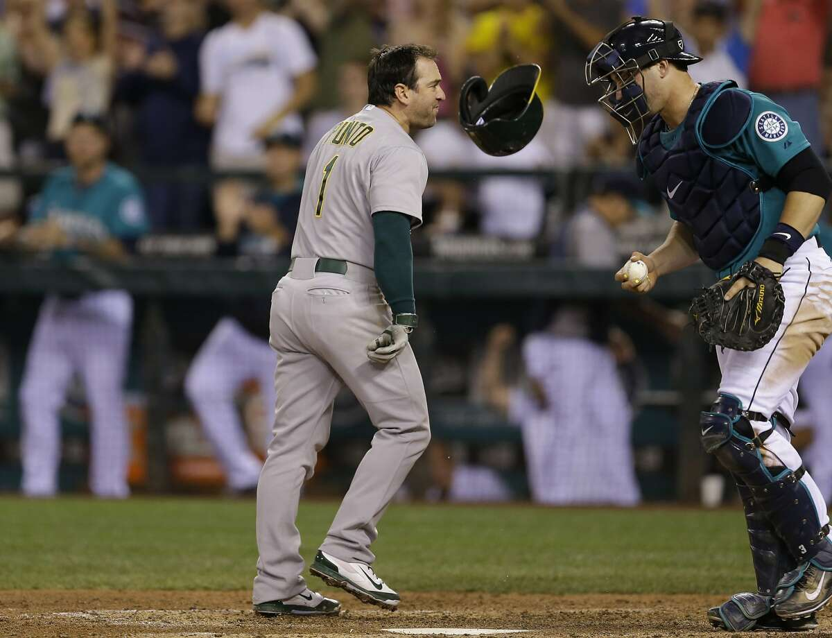 Oakland Athletics' Nick Punto's helmet bounces off the dirt in front of Seattle Mariners catcher Mike Zunino, right, after Punto threw it down when he was called out on strikes to end the ninth inning of a baseball game on Friday, July 11, 2014, in Seattle. The Mariners won 3-2. (AP Photo/Ted S. Warren)