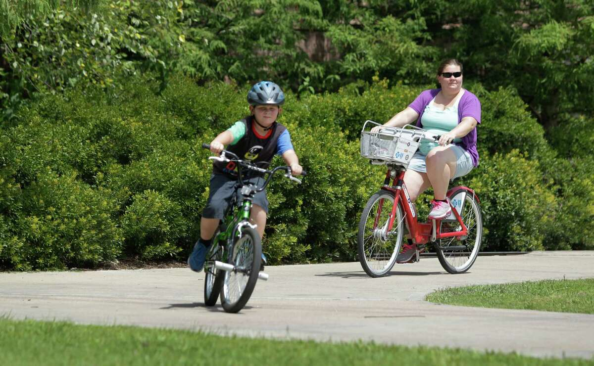 Crystal Humble, of Douglas, Ariz., rides a B-Cycle during an outing with her son, Landen Humble, 8, in Hermann Park on July 11, 2014, in Houston. The B-Cycle location at Hermann Park Lake Plaza, 6100 Hermann Park Drive, near the zoo is the city's most popular spot for picking up the recognizable bikes.