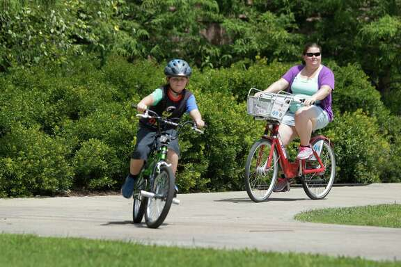 Crystal Humble, of Douglas, AZ rides a B-Cycle during an outing with her son, Landen Humble, 8, in Hermann Park Friday, July 11, 2014, in Houston. The B-Cycle location at Hermann Park Lake Plaza, 6100 Hermann Park Drive, near the zoo is the city's most popular spot for picking up the recognizable bikes.