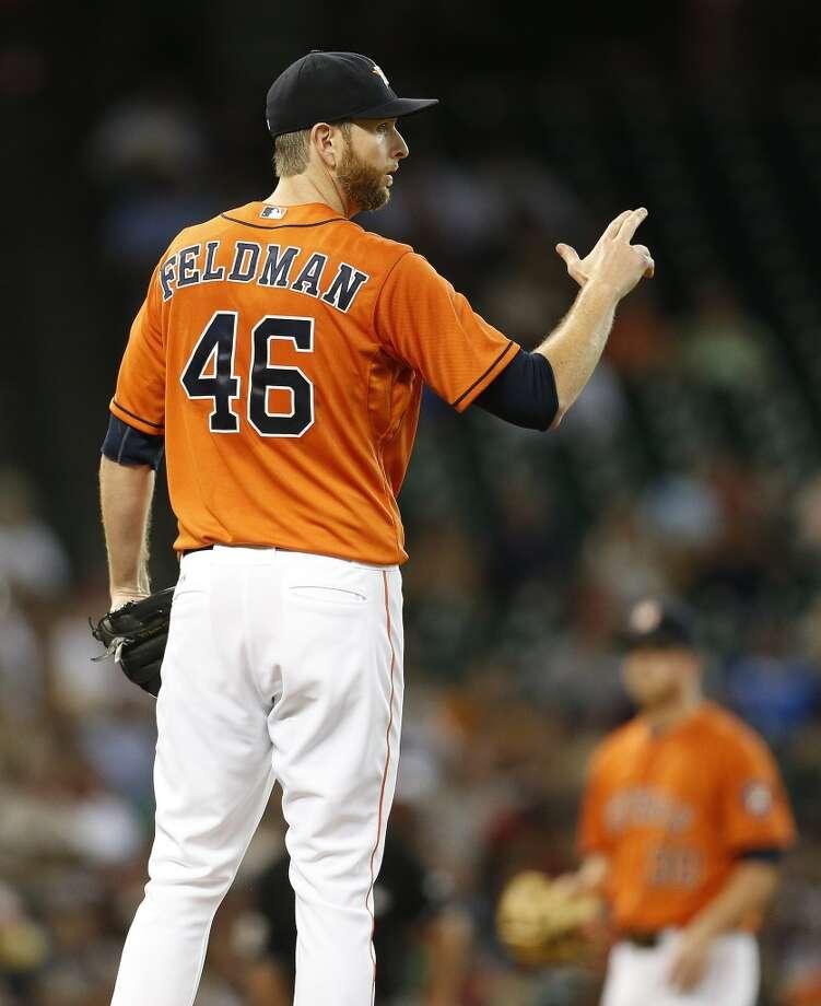 Scott Feldman (46) signals to his team in the second inning. Photo: Karen Warren, Houston Chronicle