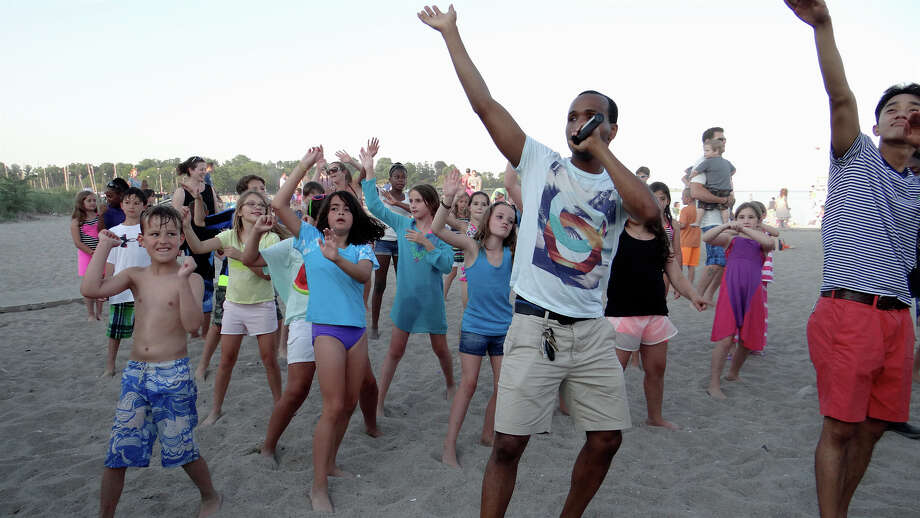 Paul Herman of Double Up Dance Group leads the crowd in dance moves Friday during the Sand Jam Movie Night at Jennings Beach. Photo: Mike Lauterborn / Fairfield Citizen