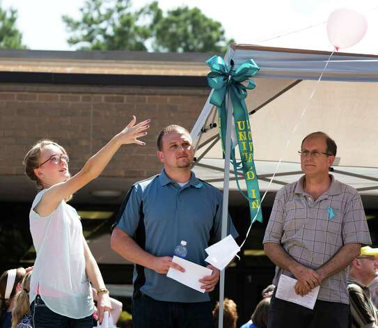 Cassidy Stay, lone survivor of the mass shooting of her parents and siblings, lets a balloon go during a community memorial celebrating the lives of the Stay family at Lemm Elementary School Saturday, July 12, 2014, in Spring. She is standing next to Drew Lyons, center, and Roger Lyons. Photo: Brett Coomer, Houston Chronicle / © 2014 Houston Chronicle