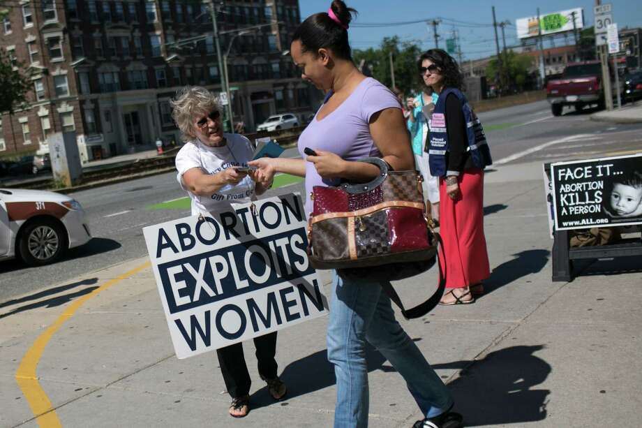 Theresa Gorey, left, hands out pamphlets in front of a Planned Parenthood office in Boston, June 27, 2014. The Supreme Court on Thursday struck down a seven-year-old Massachusetts law that created a no-protest buffer zone around abortion clinics; Boston officials plan to send police to provide additional security here in anticipation of renewed protests. (Katherine Taylor/The New York Times) ORG XMIT: XNYT123 Photo: KATHERINE TAYLOR / Katherine Taylor  www.contemporarycapture.com