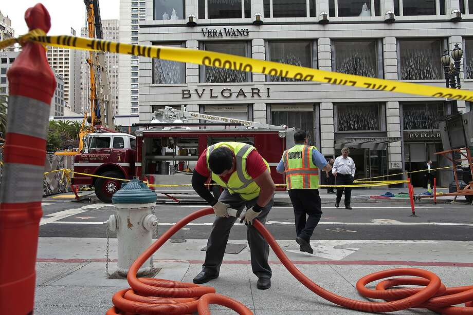 Crews work to drain the basements of businesses on Geary Street after a Central Subway project contractor broke a water main near Union Square. Photo: James Tensuan, The Chronicle
