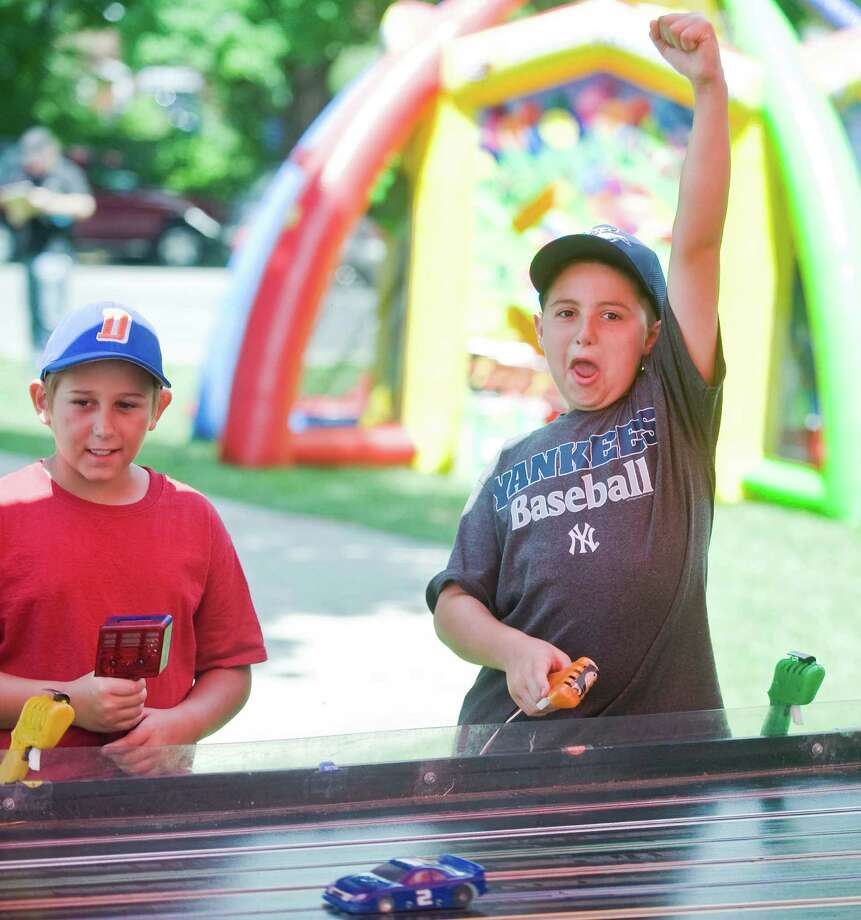 At Bethel's 36th Summer Fest on School Street, there is music, food, vendors and games for kids. Under the slot car tent, Billy Porta watches his car as Vincent Trombetto, right, wins the race. Both are 9 from Danbury. Saturday, July 12, 2014 Photo: Scott Mullin / The News-Times Freelance