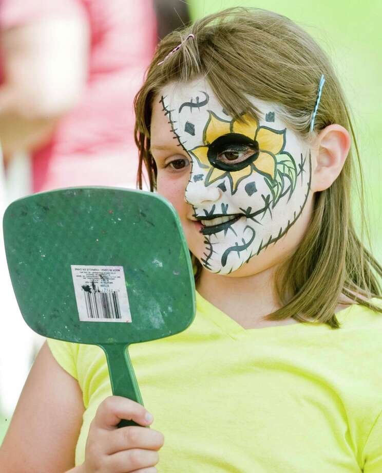 Kaydence Soule, 8, takes a look at the facial artwork at Bethel's 36th Summer Fest on School Street. Saturday, July 12, 2014 Photo: Scott Mullin / The News-Times Freelance