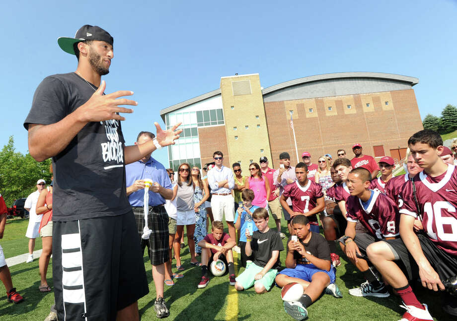 At right, Brian Kollar, 16, a St. Luke's football quarterback listens with teammates to San Francisco 49ers quarterback Colin Kaepernick, left, during his visit to the St. Luke's School in New Canaan, Conn., Saturday afternoon, July 12, 2014. Kaepernick visited the school on behalf of the Children of Fallen Patriots Foundation that provides college scholarships and educational counseling to military children who have lost a parent in the line of duty. The foundation was founded by husband and wife, David and Cynthia Kim of Greenwich. Photo: Bob Luckey / Greenwich Time