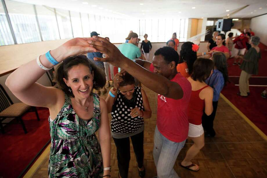 Nichole Jones, left, and Mercedes Malaga, center, dance with Raul Orlando Edwards, of Strictlly Street Salsa, during a dance lesson at the 2nd Annual Houston Symphony Free Day of Music at Jones Hall Saturday, July 12, 2014, in Houston. Photo: Brett Coomer, Houston Chronicle / © 2014 Houston Chronicle