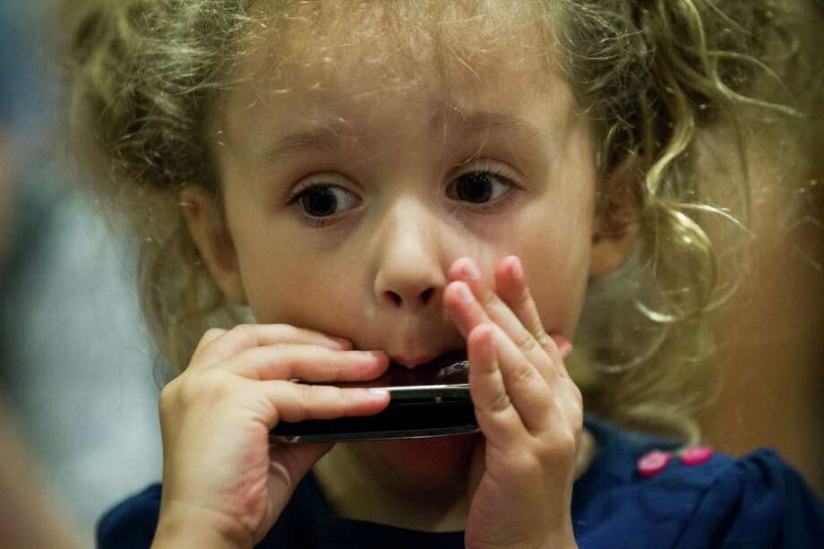 Lillian Bardo, 3, plays a harmonica as she participates in a harmonica lesson during the 2nd Annual Houston Symphony Free Day of Music at Jones Hall Saturday, July 12, 2014, in Houston. Photo: Brett Coomer, Houston Chronicle / © 2014 Houston Chronicle