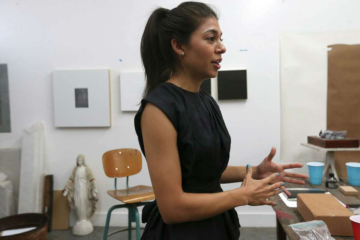 Artist Adriana Corral talks about her works while in her studio on the first level of a renovated fire station, Thursday, July 3, 2014.