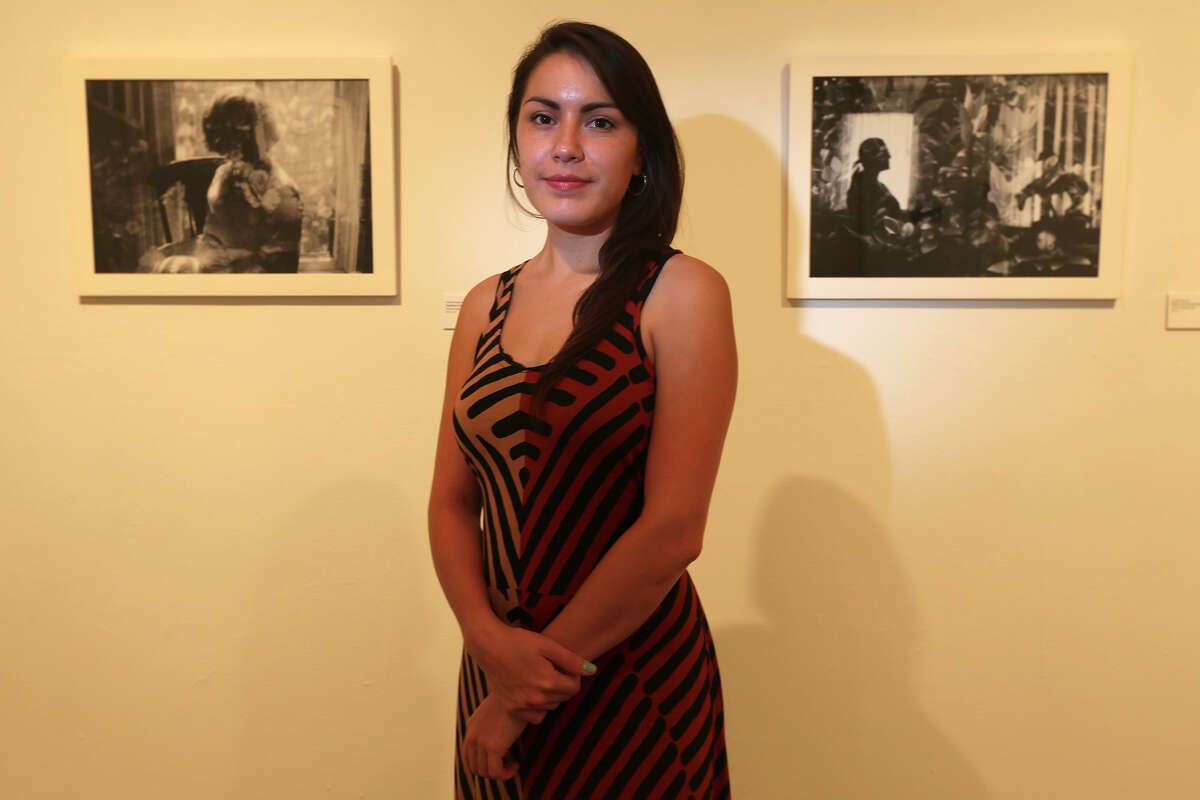 Janelle Esparza poses with her work on exhibit at the Blue Star Contemporary Art Museum, Thursday, July 3, 2014. Esparza is a photographer who used multiple exposure on her negatives to create her photographs for 'Ancestral Archetypes'.