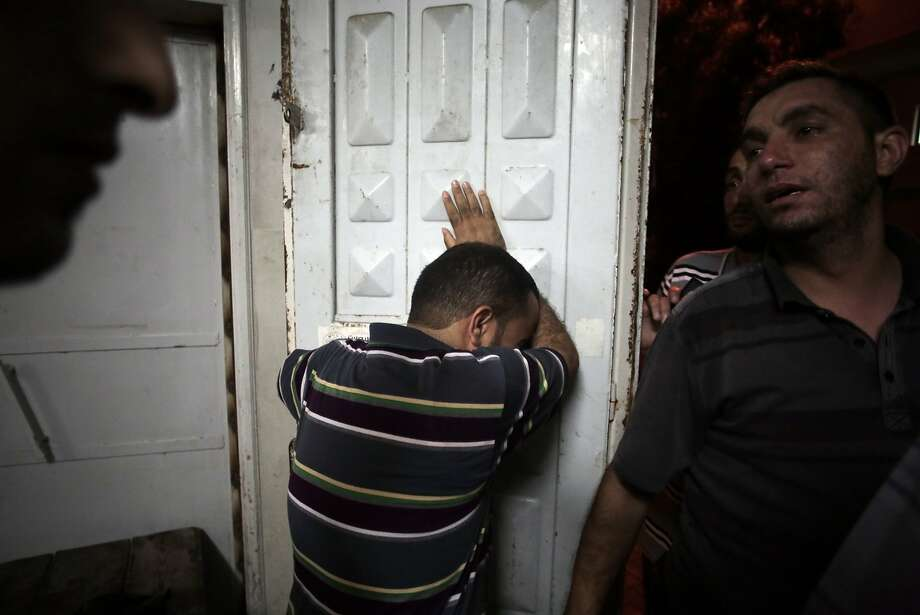 Palestinians mourn their relatives in the morgue of Shifa Hospital in Gaza City after an air strike. Photo: Khalil Hamra, Associated Press