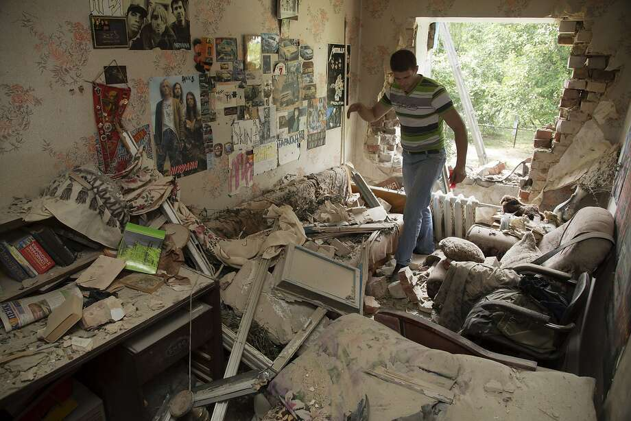 Eugeny Vaschenko walks into his shell-damaged room in Maryinka, a western suburb of Donetsk. Photo: Dmitry Lovetsky, Associated Press